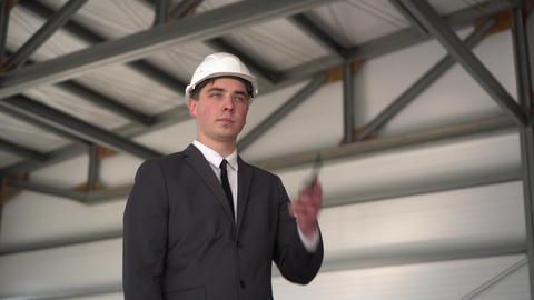 A young man in a helmet speaks on a walkie-talkie at a construction site. The ライブ動画