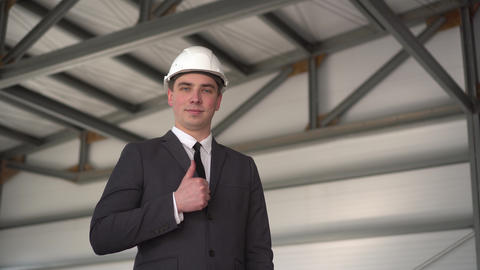 A young man in a protective helmet, shows a thumb at a construction site. The ライブ動画
