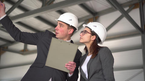 Woman approves the project. Young man and woman in helmets with documents at a Live Action