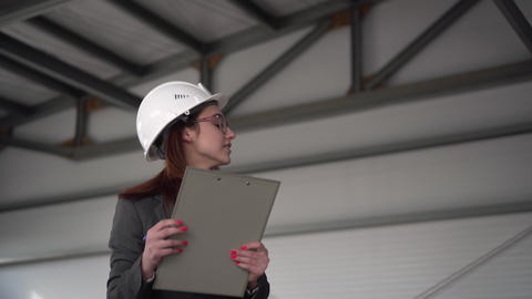 Young woman in a helmet scared off at a construction site. The boss woman in a Live Action