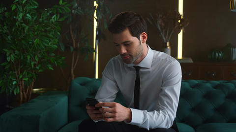 Smiling businessman browsing internet on smartphone. Ceo male using smartphone Live Action