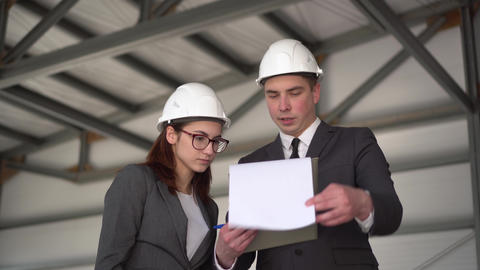 Young man and woman in helmets with documents at a construction site ライブ動画