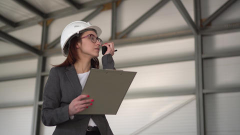 A young woman in a helmet with documents speaks on a walkie-talkie at a ライブ動画