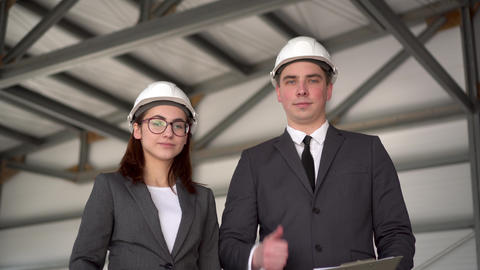 Young man and woman in helmets at a construction site. Businessmen in suits are ライブ動画
