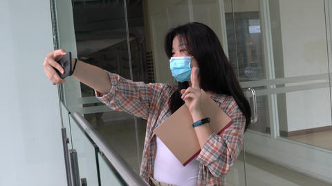 Young Chinese girl or student taking selfie with her cellphone. Smiling and happy Live Action