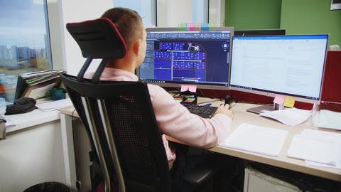 engineer draws on computer screen sitting at table in office GIF