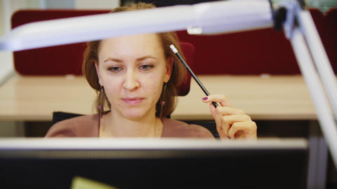 young woman turns on light working on computer in office GIF