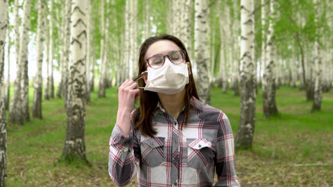 A young girl takes off a medical mask in the forest. Happy girl walks in a birch Live Action