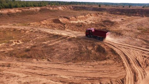 Red Dump Truck Moving On The Red Sand Road Live Action