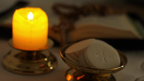 Communion hosts in twilight illuminated by the light of a lit candle rosary ライブ動画