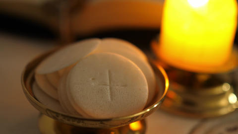 Communion hosts in twilight illuminated by the light of a lit candle ライブ動画