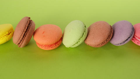 assortment of baked macarons on a green background, dessert lies in a row Live Action