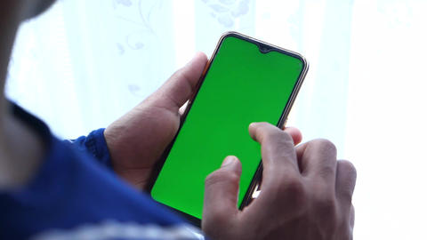back view of man holding smart phone with green screen Live Action