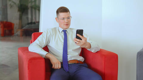 young businessman using smartphone for online call indoors Live Action