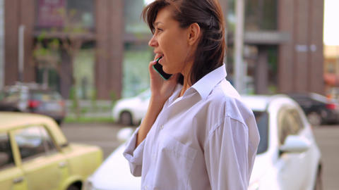 side view close up young businesswoman talking by phone walks along road Live Action