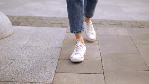 close up caucasian woman in casual shoes walks on the street Live Action