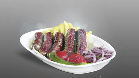 Turkish meatballs (inegol kofte) served with fried potato tomato and pepper on white plate on gray Live Action