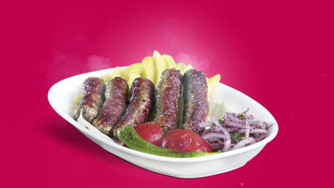 Turkish Inegol Kofte served with fried potato tomato and pepper on white plate on purple background Live Action