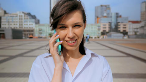 close up portrait happy smiling woman using cellphone urban city background Live Action