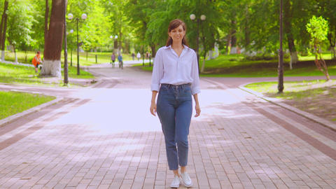 young female in white shirt and denim walk on the street in summer season Live Action