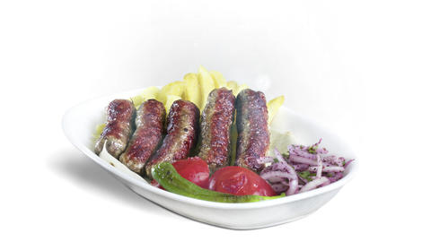Turkish Inegol Kofte served with fried potato tomato and pepper on white plate on white background Live Action