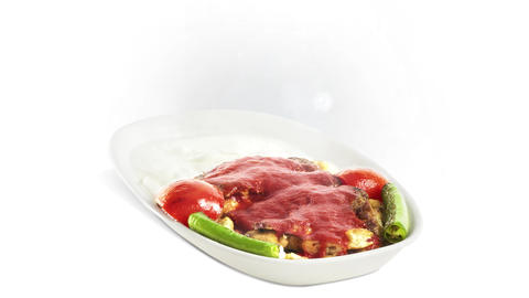 Iskender Kebab on white plate on white background direction from bottom to center Live Action