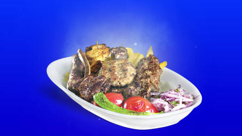 Mixed Kebab served with fried potato tomato and pepper on white plate on blue background Live Action