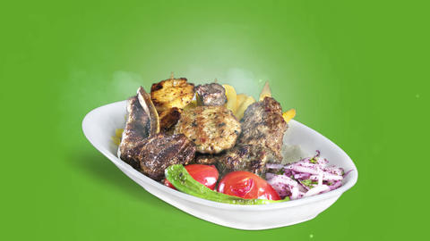 Mixed Kebab served with fried potato tomato and pepper on white plate on green background Live Action