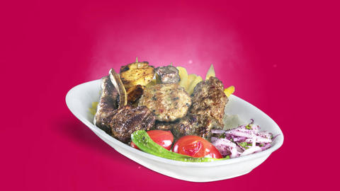 Mixed Kebab served with fried potato tomato and pepper on white plate on purple background Live Action