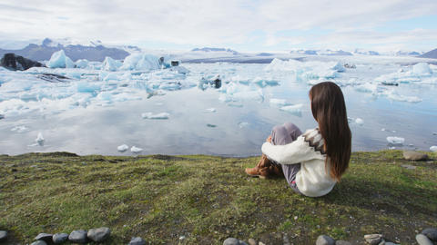 Iceland tourist enjoying Jokulsarlon glacial lagoon - ICELAND written with rocks Live Action
