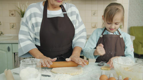 Loving grandmother cooking with child touching her nose with flour-covered Live Action