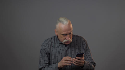 aged man holds gadget looks at telephone upsets and cries Live Action