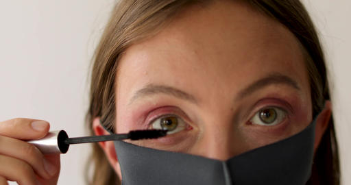 Woman in protective mask applies mascara Live Action