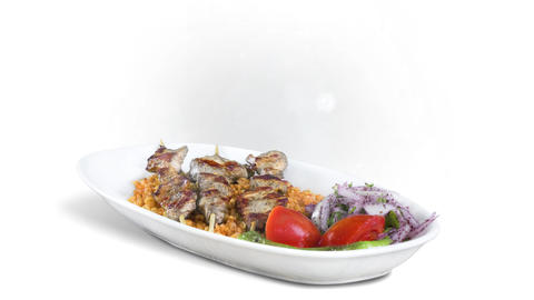 Kebab Shish on white plate on white background direction from top to center Live Action