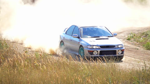 Sports Car With a Cloud of Dust on the Bend of the Rally Track. Slow Motion Acción en vivo