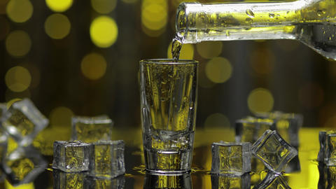 Barman pour frozen vodka from bottle into shot glass. Ice cubes against shiny Live Action