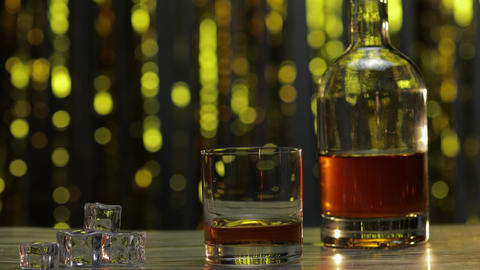 Barman adds ice cubes into glass with golden whiskey, cognac or brandy on table ライブ動画