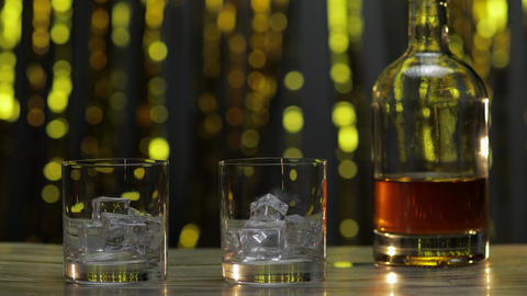 Pouring of whiskey, cognac or brandy from bottle into glasses with ice cubes ライブ動画