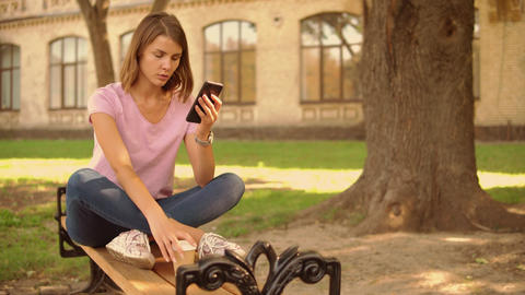 young woman use smartphone near college Live-Action