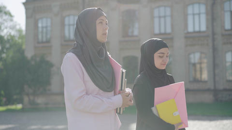 Side view portrait of two Muslim immigrants walking in sunrays at the background ライブ動画