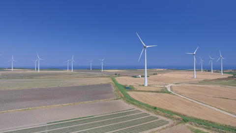 Aerial view of industrial windmills aligned in open countryside Live Action