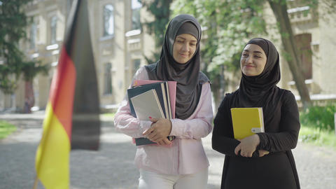 Two female Muslim immigrants standing with book on university yard and talking ライブ動画