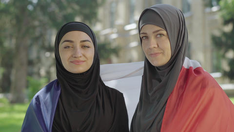Close-up of two happy Muslim immigrants wrapped in French flag posing at ライブ動画