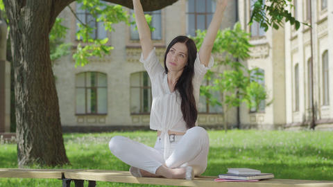 Portrait of confident young woman in white clothes relaxing in lotus pose Live Action