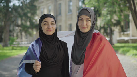 Middle shot of young Muslim women wrapped in French flag looking at camera and ライブ動画