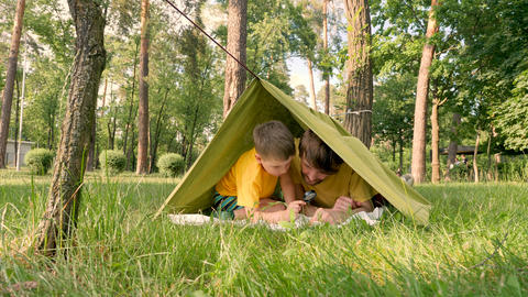 Two travelers having fun in tent. Traveling close to home. Father with son lying Live Action