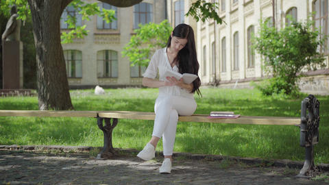 Wide shot of concentrated brunette woman in white clothes sitting on bench on ライブ動画