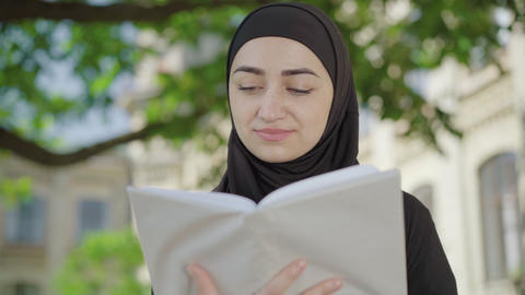 Close-up of concentrated Muslim woman reading book outdoors. Absorbed young ライブ動画