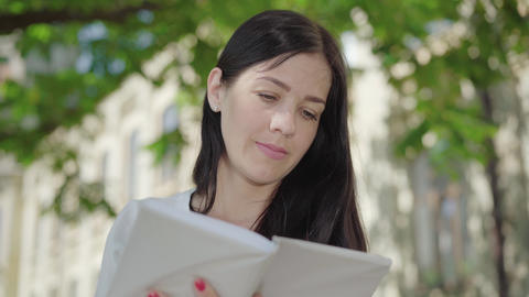 Close-up face of serious absorbed Caucasian woman reading book at university ライブ動画