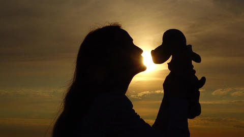 Happy woman kiss soft toy, silhouette profile portrait against sunset, slowmo Footage